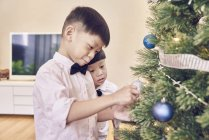 Happy asian family celebrating christmas together, boys decorating fir tree — Stock Photo