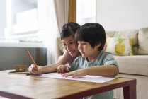 Happy young asian family together, children drawing at home — Stock Photo