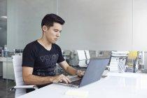 Joven empresario exitoso que trabaja en la oficina moderna - foto de stock