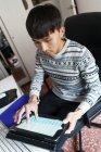 Joven adulto asiático hombre usando digital tablet en casa - foto de stock