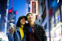 Jovem asiático casal olhando ao redor no tempo quadrado, Nova York, EUA — Fotografia de Stock