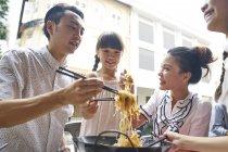 Família asiática feliz comendo macarrão juntos no café de rua — Fotografia de Stock