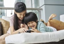 Familia asiática joven feliz juntos, niños usando digital tablet en casa - foto de stock
