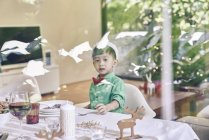Pouco ásia menino sentado no Natal tabela e sorrindo — Fotografia de Stock