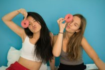 Two young women having fun with donuts — Stock Photo