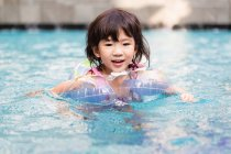 Little girl swimming in the pool with floats on. — Stock Photo