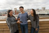 Group of Chinese friends laughing together on balcony — Stock Photo