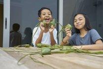 Young asian siblings celebrating Hari Raya together at home and making decorations — Stock Photo