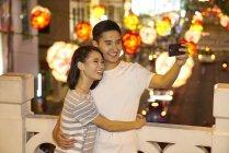 Молодые азиатские пара, проводить время вместе на традиционный базар на Китайский Новый год и принимая selfie — стоковое фото