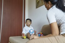 Азіатський мати і син склеювання над іграшки на дивані — стокове фото