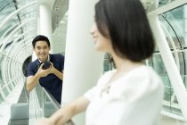 Young attractive asian couple together with camera in mall — Stock Photo
