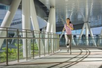 A young asian woman is jogging through the city of Singapore in the early morning. She passes a section of steel and glass architecture. — Stock Photo