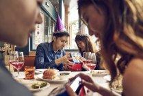 Glückliche junge asiatische Freunde gemeinsam Weihnachten zu feiern, im Café und Austausch von Geschenken — Stockfoto