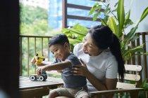 Madre asiática interactuando con su hijo en casa - foto de stock