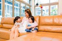 Mère et enfants utilisant une tablette à la maison — Photo de stock