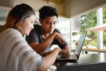 Young attractive asian couple using laptop together — Stock Photo