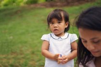 Young asian mother with cute little daughter in park — Stock Photo