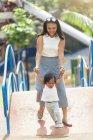 Милая очаровательная азиатская маленькая девочка в парке с мамой — стоковое фото
