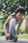 Cordones de womantying deportivo asiático joven en el Parque - foto de stock