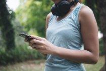 Молодая азиатская спортсменка с помощью смартфона в парке — стоковое фото