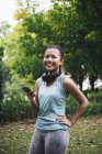 Jeune asiatique sportive femme en utilisant smartphone dans le parc — Photo de stock
