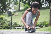 Joven deportiva de Asia con auriculares atar cordones de los zapatos en el Parque - foto de stock