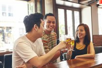 Happy young asian friends drinking beer in bar — Stock Photo