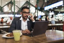 Handsome indian business man using laptop and eating in cafe — Stock Photo
