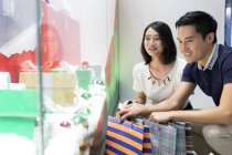Young attractive asian couple together at christmas shopping — Stock Photo
