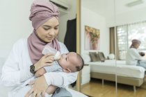 Mother feeding milk to her baby at home — Stock Photo