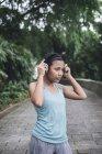 Молодая азиатская спортсменка в наушниках в парке — стоковое фото
