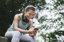 Joven mujer deportiva asiático con smartphone en Parque - foto de stock