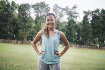 Junge asiatische sportliche Frau posiert im Park — Stockfoto