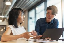 Two young asian people at work with documents in modern office — Stock Photo