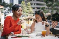 Молоді азіатські подруг разом їдять в кафе — стокове фото