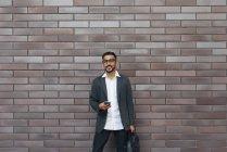 Красивый индийский бизнесмен, использующий смартфон против кирпичной стены — стоковое фото
