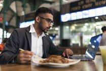 Красивый индийский бизнесмен, пользующийся ноутбуком и питающийся в кафе — стоковое фото
