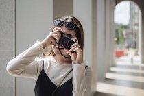 Красивая китайская женщина с длинными волосами, фотографирующая с камерой — стоковое фото