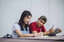 Young asian college students studying together — Stock Photo