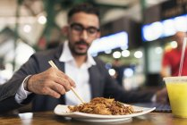 Handsome indian business man eating in cafe — Stock Photo