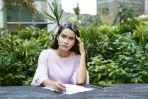 Joven dama malaya frustrada con los documentos que está mirando a través - foto de stock