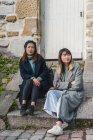 Jeunes filles asiatiques occasionnelles, assis sur les escaliers près du bâtiment — Photo de stock