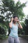 Молодая азиатская спортсменка с наушниками в парке — стоковое фото