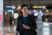 Successful asian business man using smartphone in airport — Stock Photo