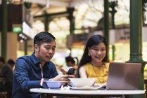 Glückliche asiatische junge Paar zusammen mit Smartphone im café — Stockfoto