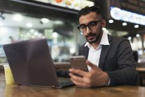Handsome indian business man using smartphone and laptop in cafe — Stock Photo