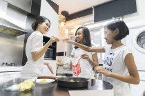 Счастливая азиатская семья празднует Хари Райя дома и приготовления пищи на кухне — стоковое фото