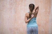 Vista posteriore della giovane donna asiatica sportiva che fa stretching — Foto stock