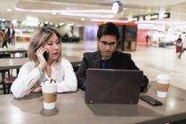 Pareja asiática de negocios exitosos junto trabajando con el portátil en el aeropuerto - foto de stock