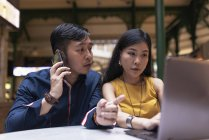 Couple jeune asiatique heureux ensemble à l'aide de portable au café — Photo de stock